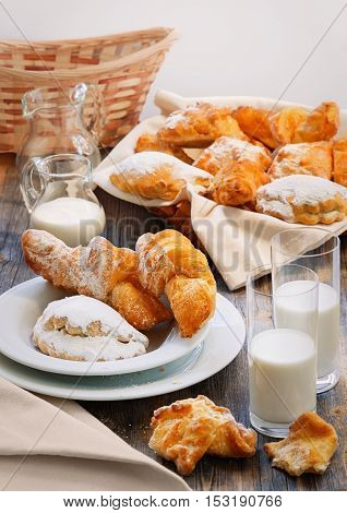 Sweet pies, jug and two glasses with milk in style a rustic