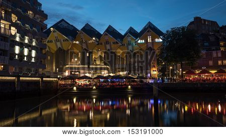 ROTTERDAM, NETHERLANDS- AUGUST 05, 2016: Night view of waterside with outdoor cafes near famous Cubes Houses, designed by architect Piet Blom