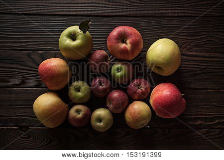 Colored apples of different sizes on a wooden surface