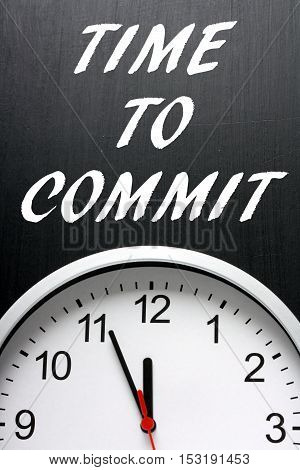 The words Time To Commit on a blackboard above a clock as a call to action when making decisions
