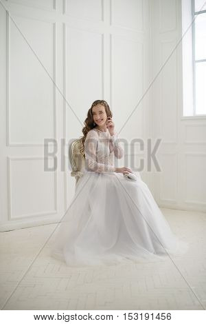 Beautiful young bride sitting on a chair in white room.