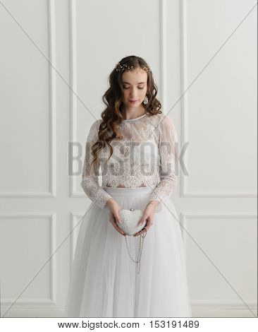 Bride standing with wedding accessories in white room.