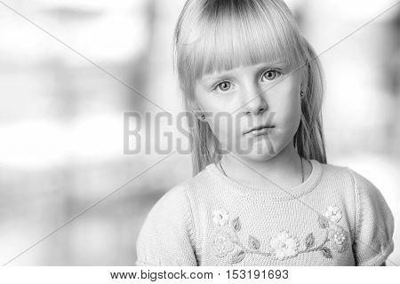 serious blond little girl looking sadly. Grey background behind