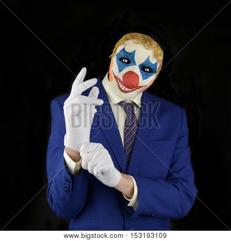 Evil clown on black background man in a clown mask dressed in a business suit wear white gloves