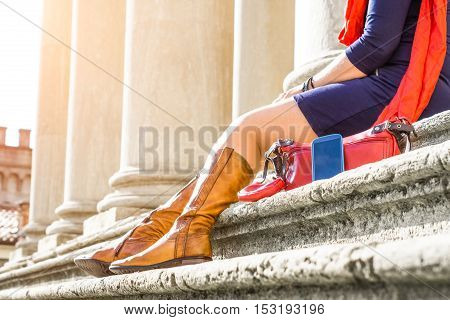 Woman on a date sitting on old monument stairs with personal belongings foreground - Cropped image of female tourist relaxing outside old building at day time - Main focus on mobile smart phone