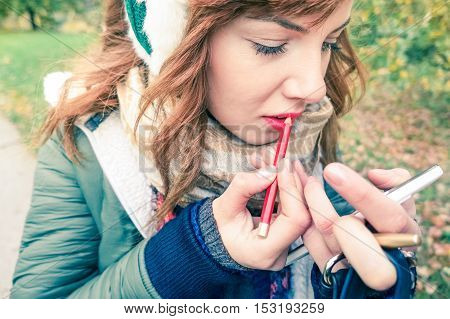 Young woman putting on makeup for lips close up image - Girl using mobile phone screen for beauty retouching in a winter day outdoors scene - Concept of female natural gestures in everyday life