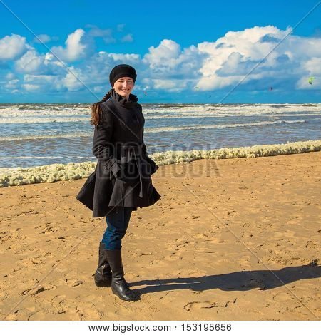 Smiling happy woman dressed in a coat at the beach of cold sea. Sea vacations.