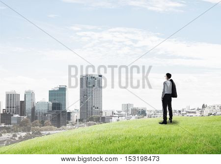 Businessman standing with back on top of hill and viewing modern city