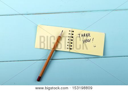 Thank You pencil and A spiral Notepad that has the words Thank You over a distressed wood turquoise background