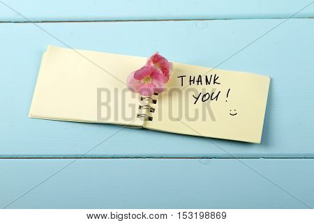 Thank You flower A spiral Notepad that has the words Thank You over a distressed wood turquoise background
