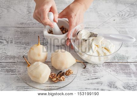 Woman In Kitchen Using Mortar And Pestle