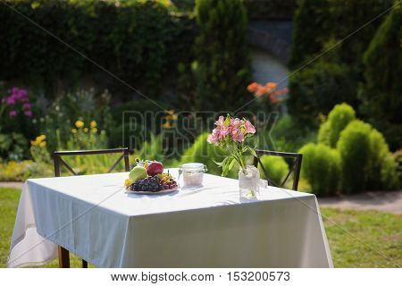Beautiful terrace with small table, chair and flowers. Delicious fruints represented on cottage table outdoors.