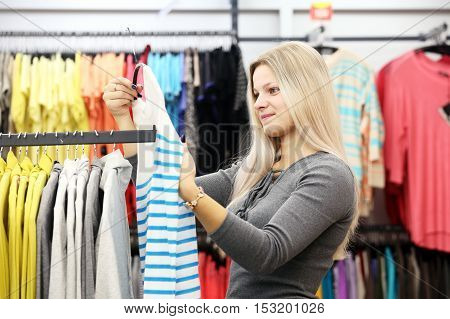 Happy woman choosing clothes in clothing store. Girl in clothes shop