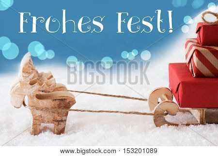 Moose Is Drawing A Sled With Red Gifts Or Presents In Snow. Christmas Card For Seasons Greetings. Light Blue Background With Bokeh Effect. German Text Frohe Fest Means Merry Christmas