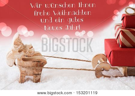 German Text Wir Wuenschen Ihnen Frohe Weihnachten Und Ein Gutes Neues Jahr Means Merry Christmas And Happy New Year. Moose With Sled With Gifts In Snow. Red Christmassy Background With Bokeh Effect.