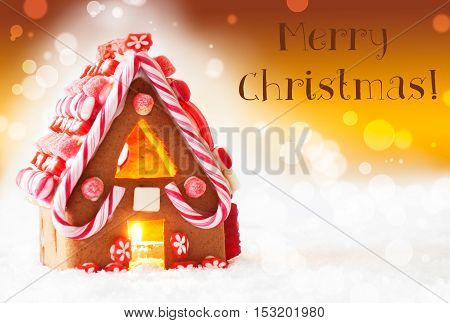 Gingerbread House In Snowy Scenery As Christmas Decoration. Candlelight For Romantic Atmosphere. Golden Background With Bokeh Effect. English Text Merry Christmas