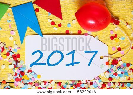 White Label With Text 2017 For Happy New Year. Close Up Of Party Decoration Like Streamer, Confetti And Balloon. Flat Lay Or Top View. Yellow Wooden Background