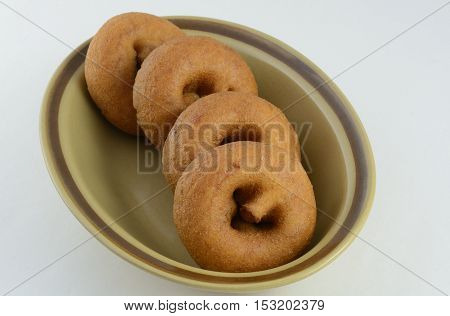 Plain breakfast donuts in brown bowl against white background