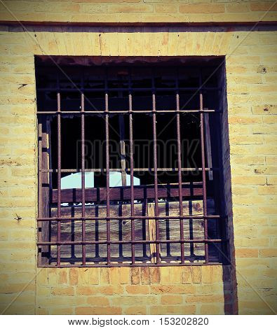 Broken Window Of An Abandoned House With Iron Bars A