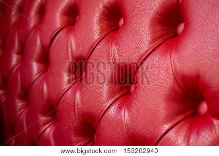 Texture of red leather sofa. Focus on the center