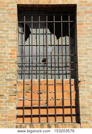 Broken Window Of An Abandoned House With Iron Bars