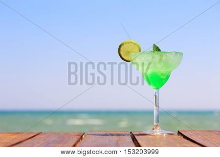 Green Fairy Cocktail On The Wooden Pier. Concept Of Exotic Cocktail. Seaside Vacation