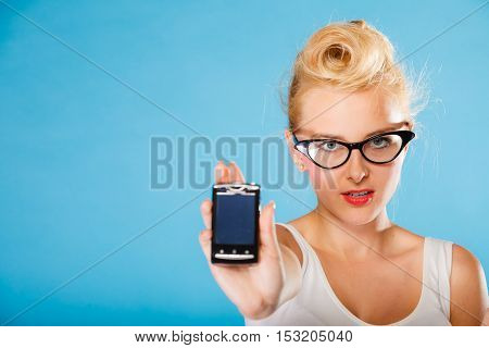 Librarian accountant and secretary concept. Retro pin up style. Young blonde woman in glasses. Girl holding smartphone on blue background in studio.