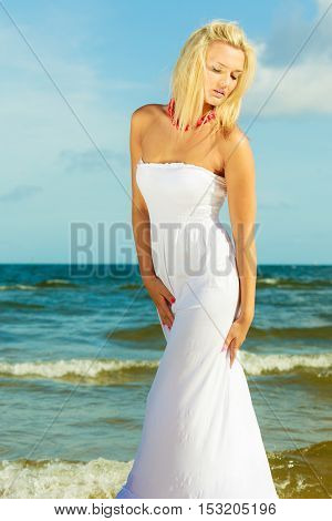 Girl taking walk on shore. Young elegant woman in white dress. Outdoor leisure relax concept.