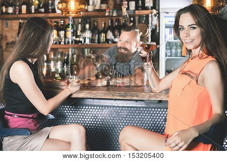 Beautiful girl is drinking a cocktail in the bar with her friend. Nightclub. Handsome bartender talking with young woman