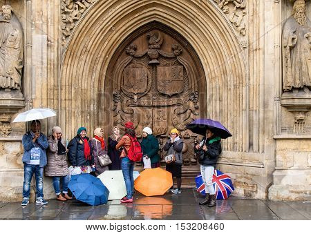 BATH, UK - OCTOBER 24 2016 Asian tourists sheltering from rain in Somerset. Visitors to the UNESCO World Heritage City hide under umbrellas in the arched doorway of Bath Abbey, with Union Jack
