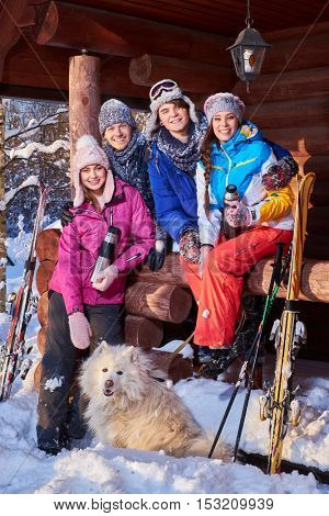 Cheerful friends with dog spend winter holidays together at mountain cottage
