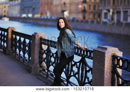 Pretty serious girl in denim jacket standing on the St. Petersburg waterfront leaning against the iron railing and looking into the camera.
