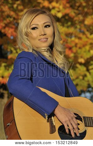 Autumn portrait of beautiful asian woman with gutar