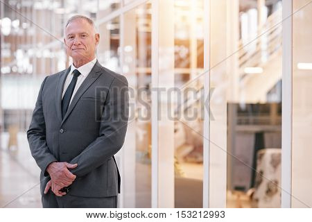 Portrait of a confident mature businessman in a suit standing in the lobby of a modern office building