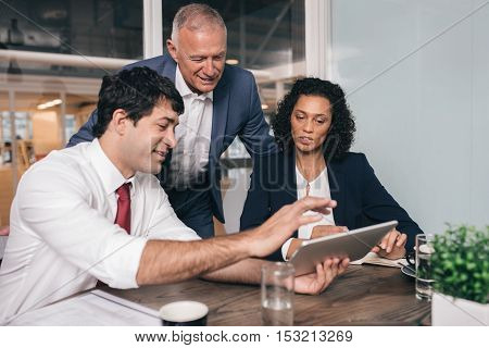 Three diverse businesspeople talking together over a digital tablet while working at a table in an office boardroom