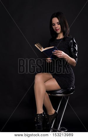 girl in a black dress with a book