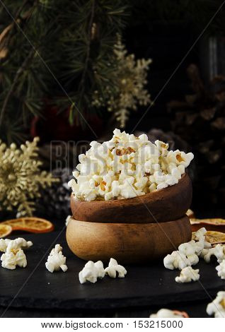 popcorn in a wooden plate on the background of Christmas trees and Christmas decorations, New Year offer, selective focus