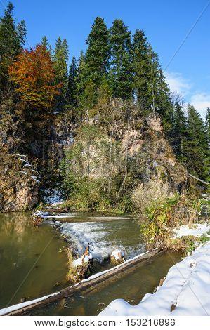 Small rapids at Lacul Rosu, the Red Lake or Killer Lake, Eastern Carpathians, Transylvania, Romania at autumn