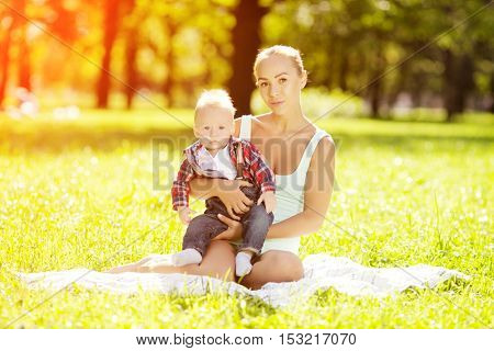 Cute little baby in the park with mother on the grass. Sweet baby and mom  outdoors. Smiling emotional kid with mum on a walk. Smile of a child