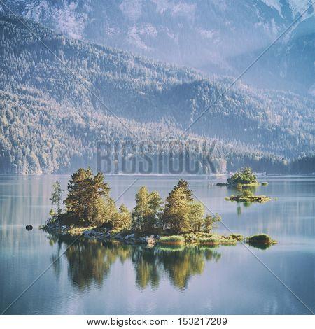 Fantastic sunrise on mountain lake Eibsee, located in the Bavaria, Germany. Dramatic unusual scene. Alps, Europe. Toned like Instagram filter