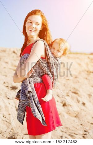 Beautiful woman with a baby in a sling. Mom and baby. Mother and child