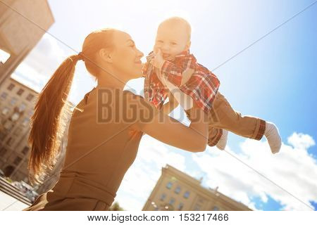 Trendy modern mother on a city street, urban landscape. Young mother walks with a child in 