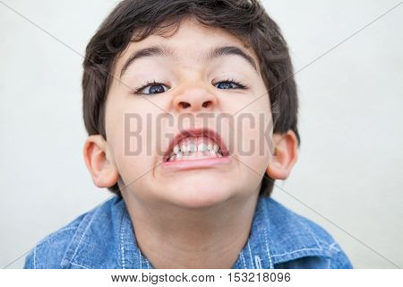 Upset young boy grimacing and showing his teeth