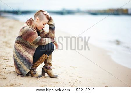 Young stylish girl with very short hair wearing a knitted cardigan sits on his haunches the sandy Bank of Neva river in fall. Side view.