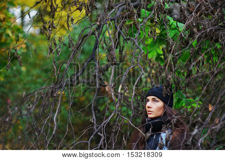 Serious cute long-haired brunette with brown eyes in a scarf and hat in the Park among the branches with dried leaves.