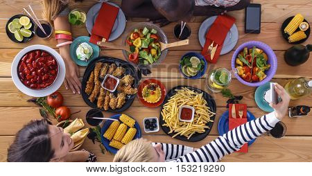 Top view of group people having dinner together while sitting at wooden table