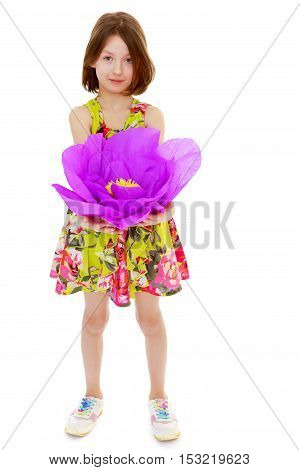 Adorable little girl in summer dress holding a large purple flower made of paper.Isolated on white background.