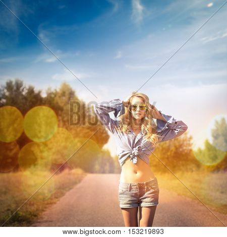 Sexy Blonde Woman with Hands behind her Head Walking on Country Road. Summer Girl Portrait. Toned and Filtered Photo with Bokeh. Hipster Style.