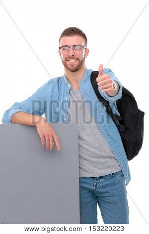 Portrait of a smiling male student holding blank board and showing ok
