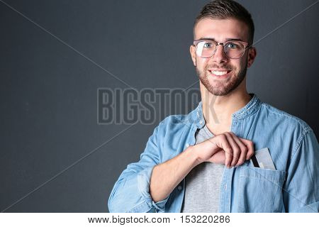 Young man holding a credit card standing on gray background